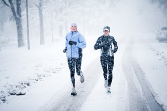 Kara Roy (black jacket) and Jennifer Lee (blue jacket) run down Mountain Avenue in a snowstorm.