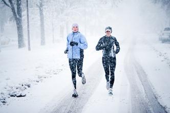 Kara Roy (black jacket) and Jennifer Lee (blue jacket) run down Mountain Avenue in a snowstorm.